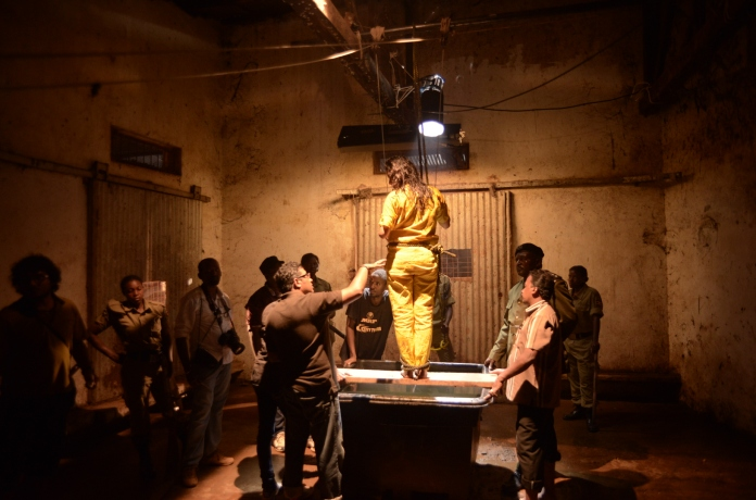A behind-the-scenes photo shows the film's lead character preparing to be hanged.